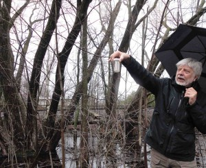 David Fletcher holds up a water sample containing mollusks. Behind him is one of many ephemeral wetlands that are important for local wildlife.